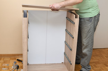 Man assembling elements of a new piece of furniture with drawers - how to build a cabinet