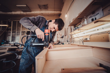 Man builds furniture in the carpentry shop - how to build a cabinet