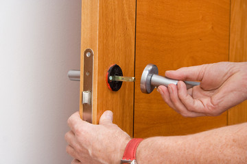 handyman repairs a door handle - how to build a door