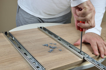 Man holding a screwdriver and installing drawer slides on an element of a chest of drawers- how to make drawers